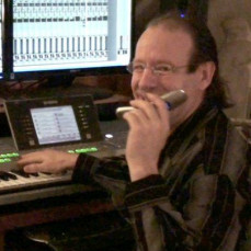 Mark in his studio, talking on the phone. - Kevin Simnacher