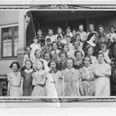 Marian shown in St. John's elementary school class with Sister Joanella (sp?). Marian 3rd from left in the bottom (1st) row and is standing between Tunnie Kelly and June Frieberger - Bill Rammer